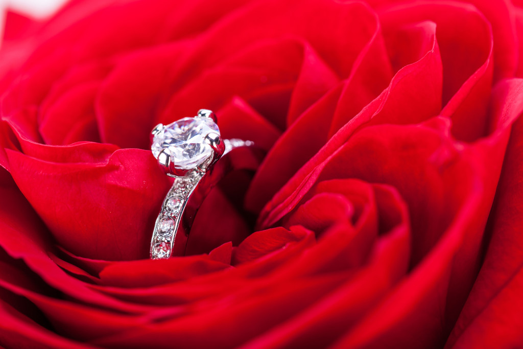 Overhead view of a diamond engagement ring nestling in the heart of a red rose amongst the soft petals ** Note: Slight blurriness, best at smaller sizes